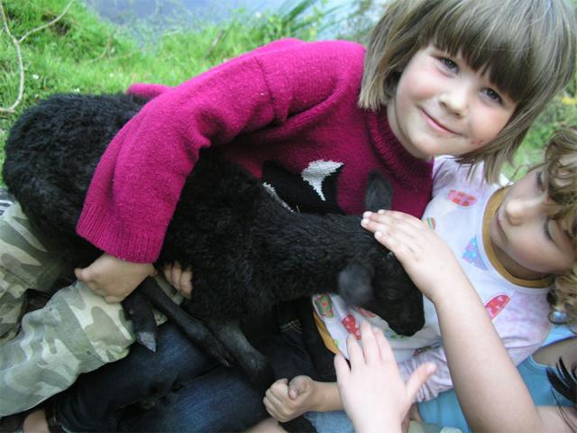 Kinder mit Lämmchen im Arm